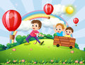 Boys playing at the hilltop with rainbow illustration of three a and floating balloons Stock Image