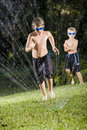 Boys playing with lawn sprinkler Royalty Free Stock Image