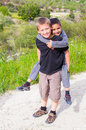 Boys playing piggyback happy smiling children race outdoors Stock Photos