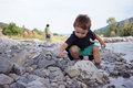 Boys playing and throwing rocks at the river with pebbles in mountains during summer Stock Images