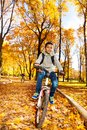 Boys ride in autumn park handsome years old black boy riding a bicycle the with his brother over orange maple and oak leaves on Stock Photos