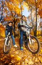 Boys rides bicycles in the park two cute black smiling and years old ride wearing helmet autumn maple and oak tree Royalty Free Stock Photos