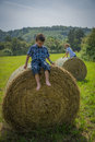 Boys on round hay bales two sitting Royalty Free Stock Photos