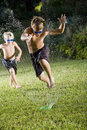 Boys running fast through lawn sprinkler Royalty Free Stock Photos