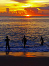 Boys in the sea at sunset Stock Photos