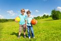 Boys sport boys two brothers kids stand with holding balls standing in the park on sunny summer day Stock Photography