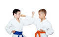 Boys sportsmen with orange and blue belt training paired exercises Royalty Free Stock Image