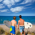 Boys teen surfers rear view looking at beach back from uo dune Royalty Free Stock Images