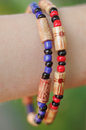 Bracelet on the wrist with wooden beads colored Royalty Free Stock Image