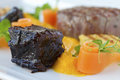 Braised pork cheeks with polenta carrot and thyme high angle view Royalty Free Stock Image