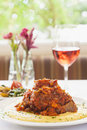 Braised veal on bed of polenta with a glass of wine in tomato sauce Royalty Free Stock Photos