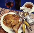 Braised veal a piece of in a white plate with some onion ring on it a nd a glass of wine and a bottle on ther side with a sauce Stock Photo