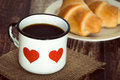 Brakfast coffee in an old enamel mug a cup of black breakfast croissants on background vintage rustic table Stock Photos