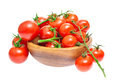 The branch of cherry tomatoes in a wooden bowl. Stock Photo