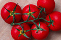 Branch of fleshy tomatoes on a wooden table closeup Stock Photos