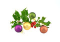 Branch of fresh holly with christmas baubles Stock Image
