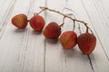 Branch of fresh lichees on white wood