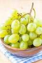 Branch of green fresh grapes in a wooden bowl on blue towel Stock Photography