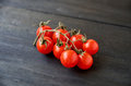 Branch of red cherry tomatoes isolated on black wooden background close up Royalty Free Stock Photo