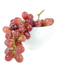Branch of red grape in white bowl on white background Stock Image