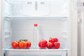 Branch of red tomatoes two red peppers two two colored orange and red peaches and a bottle of water on shelf of open empty refri Stock Image
