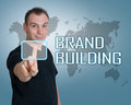 Brand building young man press digital button on interface in front of him Royalty Free Stock Photo