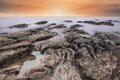 Brand new day silky smooth sea with rocks at sunrise Royalty Free Stock Images
