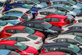 Title: Brand new motor vehicles crowed in a parking lot