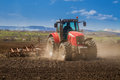 Brand new red tractor working on the field Royalty Free Stock Photos