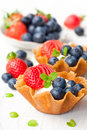 Brandy  snaps baskets with soft cream cheese and berries on whit Royalty Free Stock Photo