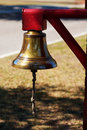 Brass bell hanging from red post Royalty Free Stock Photos