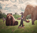 Brave child in field with wild animals a is standing a nature around him such as a bear elephant zebra and bear for an imagination Stock Photo