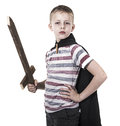 Brave little kid playing knight dressed up with cape and wooden sword hero or looking up or concept of great expectations Stock Photos