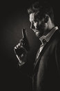 Brave man with handgun cool holding a gun on dark background Royalty Free Stock Photography