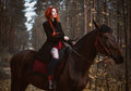 Brave red-haired girl in a black coat and a red dress with long hair gathered in a braid Royalty Free Stock Photo