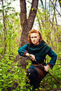 Brave scandinavian woman redhead posing with sword in a forest Stock Images