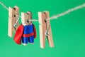 Brave superhero wooden clothespins. Team leader character in blue suit red cape. green background, selective focus