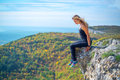 Bravery brave girl sitting on the edge of a cliff and looking down Stock Images