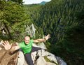 Bravery happy man sitting on the edge of a very high cliff Stock Photo