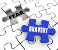 Bravery vs fear puzzle piece filling hole courage confidence word on a about to fill the word conquering adversity and being bold Royalty Free Stock Images