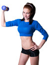 Brawny girl with dumbbell pretty happy sporty young woman model in blue top and black shorts lifting up smiling cheerfully toothy Royalty Free Stock Photo