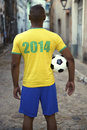Brazil football player soccer ball on street brazilian in shirt stands holding a an old rustic village Royalty Free Stock Images