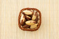 Brazil nuts in pretty little basket top view of a and bamboo mat as background Royalty Free Stock Images