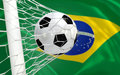 Brazil waving flag and soccer ball in goal net football Stock Photos