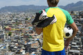 Braziliaanse voetbalster in kit holding soccer ball favela Stock Foto