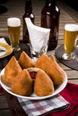 Brazilian coxinha a snack with a bar in the background Stock Photos