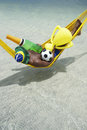 Brazilian dreaming of winning football championship a win with champagne and trophy in his hammock Royalty Free Stock Photo