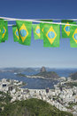 Brazilian flag bunting rio de janeiro skyline scenic overlook flying above of city with sugarloaf mountain botafogo and guanabara Royalty Free Stock Photography