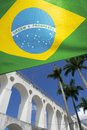 Brazilian flag at lapa arches rio de janeiro brazil flies under bright tropical blue sky with palm trees Royalty Free Stock Photo