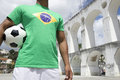 Brazilian football player holding soccer ball rio lapa wearing flag shirt at arches in de janeiro Stock Image